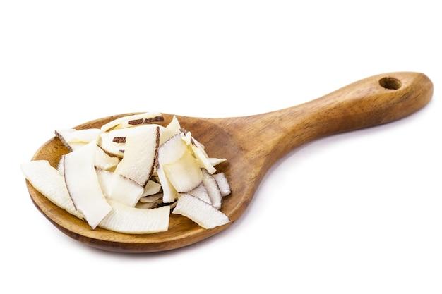 Деревенская деревянная ложка с измельченным кокосом, кокосовой стружкой, изолированной белой предпосылкой.