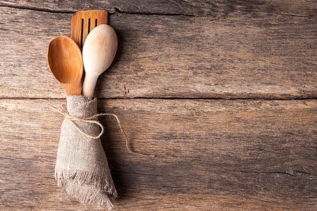 古い木製のテーブルで素朴な木製のスプーン
