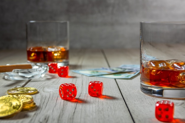 Rustic wooden table. cigar in an ashtray and two glasses of whiskey with ice cubes. dice and dollar bills. few bitcoin Premium Photo