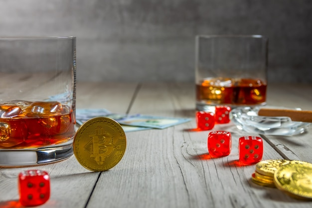 Rustic wooden table. dice and dollar bills. two glasses of whiskey with ice cubes and a cigar in an ashtray. few bitcoin