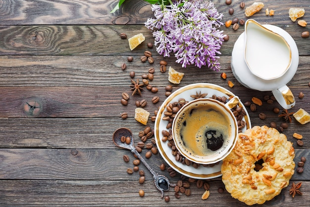 Rustic wooden table with cup of coffee, milk, peanut tart, sugar ginger and lilac flowers