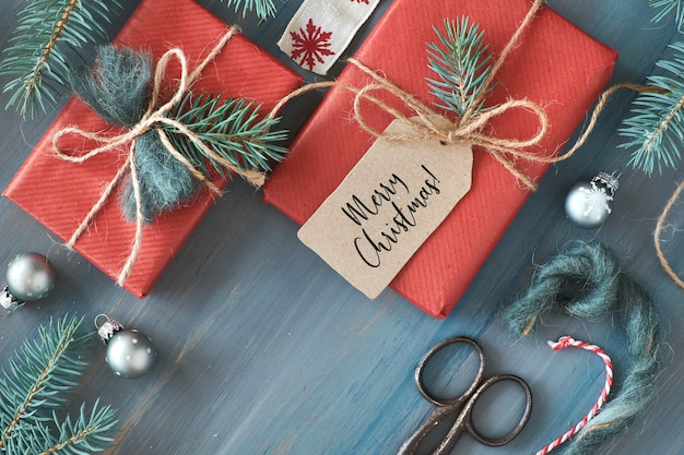 Rustic wooden table with fir branches and christmas presents gift wrapped in red paper
