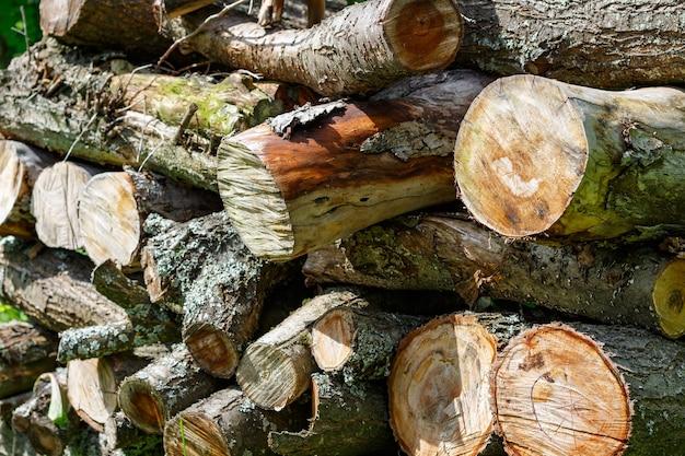 薪のクローズアップの素朴なウッドパイル。抽象的な背景