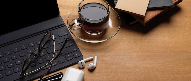 Rustic worktable with digital tablet, glasses, wireless earphone, schedule books and coffee cup
