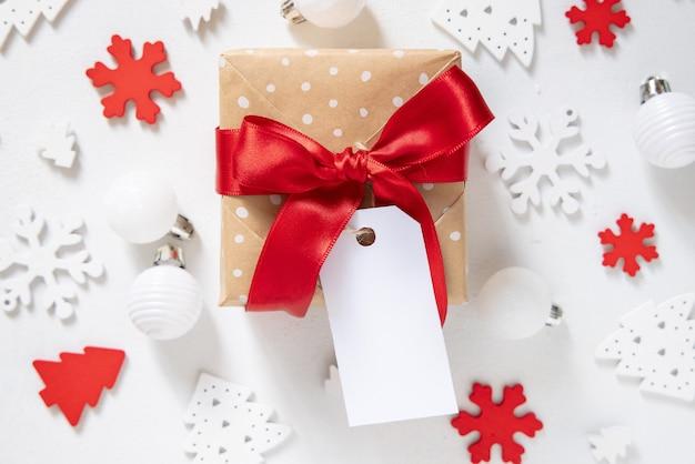 Подарочная коробка в деревенском стиле с красным бантом и бумажной подарочной биркой с белыми рождественскими украшениями