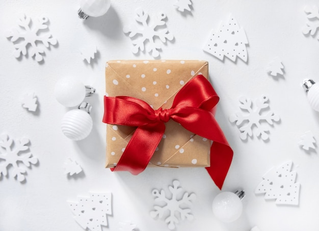 Обернутая в деревенском стиле подарочная коробка с красным бантом из ленты на белом столе с белыми рождественскими украшениями вокруг вида сверху. зимняя композиция