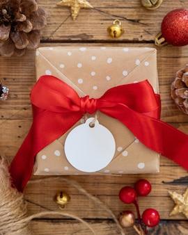 Обернутая в деревенском стиле подарочная коробка с бумажной подарочной биркой на коричневом деревянном столе с красными и золотыми рождественскими украшениями вокруг вида сверху. скандинавская зимняя композиция с пустой подарочной биркой mockup, копией пространства