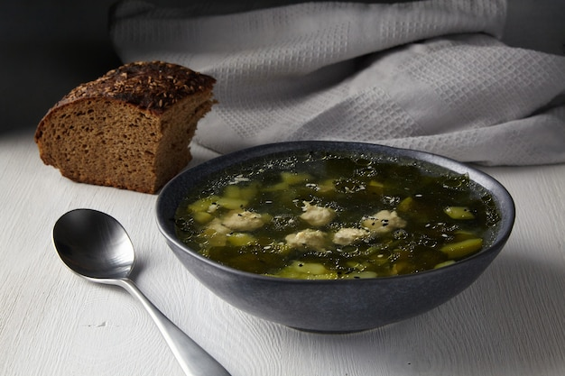 Rustic zucchini soup with meatballs with a piece of black bread with caraway seeds on a white table against the background of a gray kitchen towel in the morning light