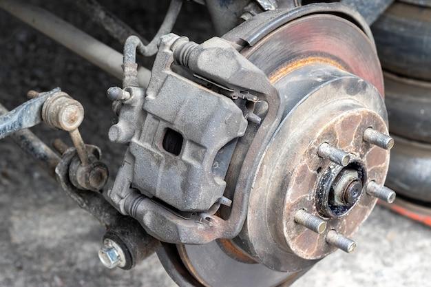 바퀴가 없는 타이어 가게 차에서 브레이크 디스크가 있는 녹슨 뒷바퀴 허브