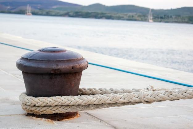 ロープ付きの港の壁にあるラスティなボート係留