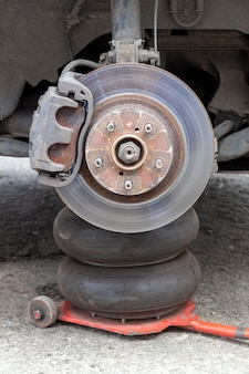 Rusty car wheel hub with brake disc at tire shop
