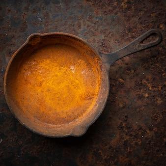 Ржавая чугунная сковорода на фоне текстуры грязной ржавой металлической пластины в квадратном соотношении, вид сверху