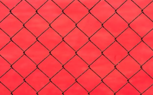 Ржавый забор звена цепи на красном фоне размытия, неглубокий фокус