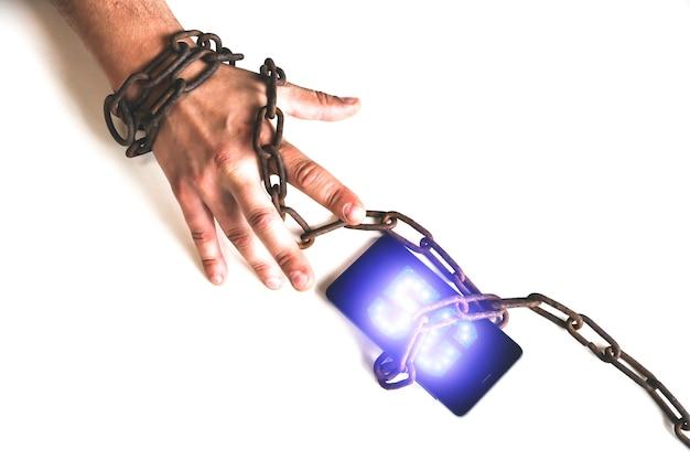 손으로 스마트폰 5g 기호 주위의 녹슨 사슬. 현대 기술에 중독되었습니다. 위험한 연결. 방지 개념입니다.