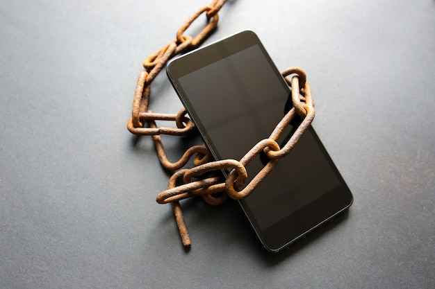 스마트폰 주변의 녹슨 사슬. 현대 기술에 중독되었습니다.