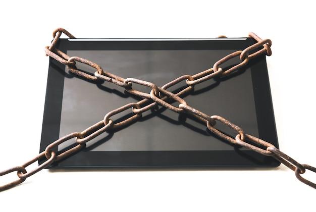 태블릿 주위에 녹슨 사슬이 있습니다. 현대 기술에 중독되었습니다.