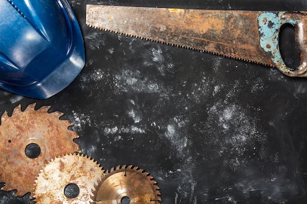 Rusty circular saw blades, saw and safety helmet on dark stone  background