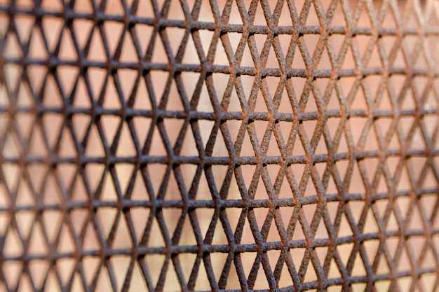 Rusty fence made of metal mesh, rhombic cells. soft focus. side view