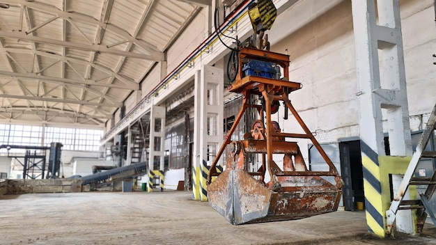 Rusty grab bucket or clamshell on overhead crane in empty industrial plant