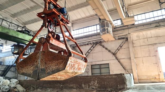 空の産業プラントの天井クレーンにぶら下がっているさびたグラブバケツまたはクラムシェル。