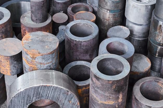 Ржавые заготовки метизов для деталей бурильной колонны лежат на полу в полутемной мастерской