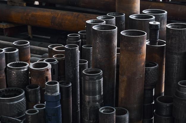 Ржавые детали оборудования турбобуров разного диаметра на полу в мастерской