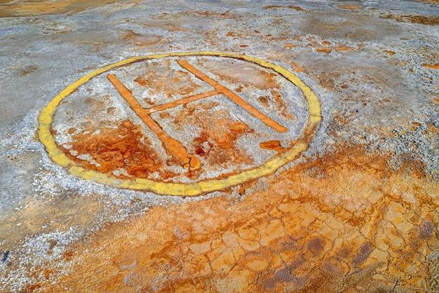 버려진 광산 지역의 오염된 땅 위에 녹슨 헬기 착륙장 표지판, 디스토피아 배경