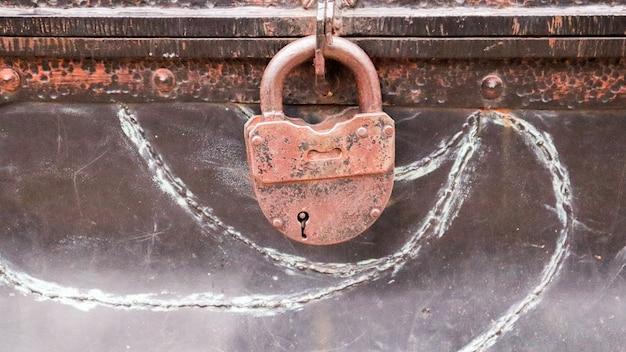 古代の嚢胞のさびた鉄の城。古い箱にぶら下がっている古い金属製の城の小屋のクローズアップ。アンティークの宝箱、アンティークのチェスト。海賊の宝箱。 Premium写真