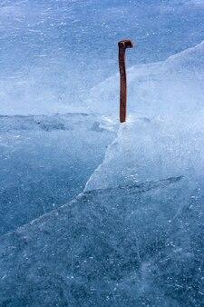 Ржавый железный старый железнодорожный костыль вбит в лед. синий тающий лед с трещинами и пузырьками воздуха. символ стойкости и стойкости. вертикальный.