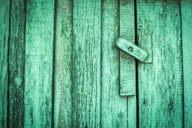 Ржавый замок на текстуре старой, деревянной, зеленой, морской двери, от которой отслаивается старая краска. проход закрыт. заперто