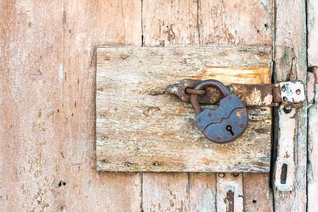 Ржавый замок на текстуре старой деревянной оранжевой двери, от которой отслаивается старая бежевая краска. проход закрыт. заблокирован.