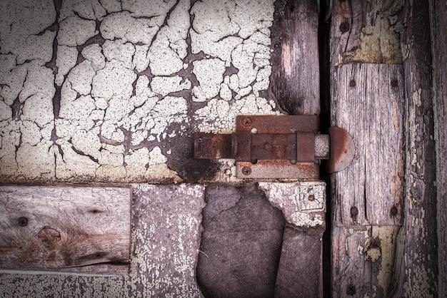 Ржавый замок на текстуре старой, деревянной, розовой, пурпурной, коричневой двери, от которой отслаивается старая краска. проход закрыт. заблокирован. место для текста