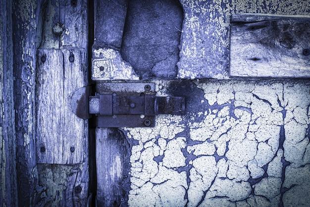 오래된 페인트가 벗겨지는 오래된, 나무, 자주색, 문의 질감에 녹슨 자물쇠. 통로가 닫힙니다. 잠긴. 텍스트를 위한 장소