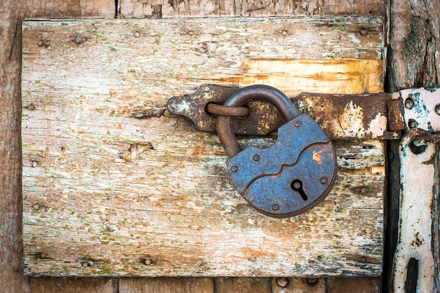 Rusty lock on a texture of old, orange door, which the old beige paint flaking. the passage is closed. locked.