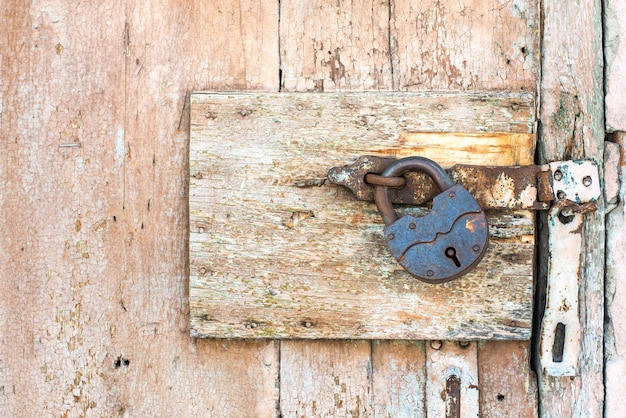 Rusty lock on a texture of old, wooden, orange door, which the old beige paint flaking. the passage is closed. locked.