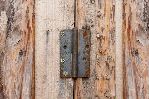 Петля дверная из ржавого металла. петля дверная на деревянной стене.