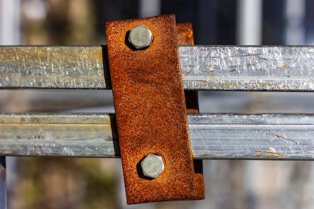 볼트가 있는 녹슨 금속 플레이트 스테인리스 스틸 프로필에 녹슨 금속 마운트가 닫혀 있습니다. 프리미엄 사진