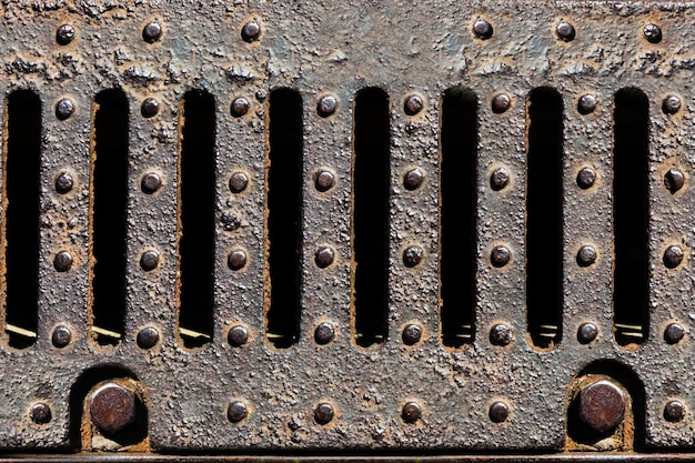 Rusty metal sewer grate close-up
