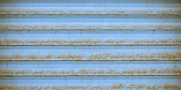 Rusty metal striped surface of jalousie, blue metallic ribbed fence, striated wall texture. urban grunge background with straight lines. exterior element.