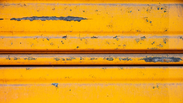 Rusty metallic wall with yellow paint