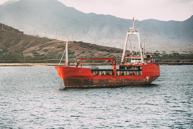 바다의 중간에 녹슨 오래 된 보트
