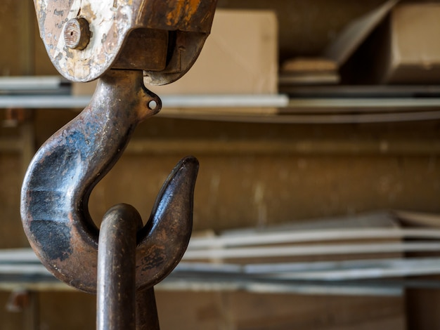 A rusty old hook from a crane in the factory.