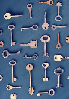 Rusty old keys locks on dark wooden background