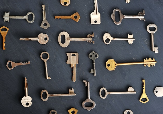 Rusty old keys locks on dark wooden rustic background