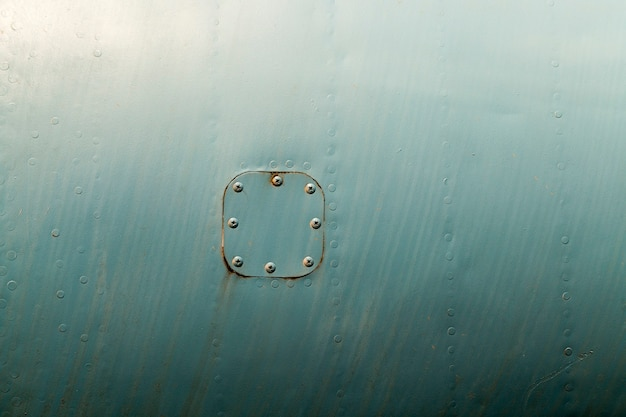 Rusty old metal hatch attached by rivets to an iron sheet