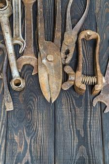 검은색 빈티지 나무 배경 작업 후 쌓인 녹슨 오래된 도구