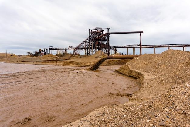 川岸のさびたパイプと静止したさびた重力砂と砂利の分離器