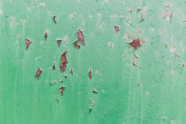 さびた赤と傷のある緑の壁