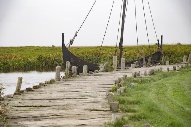 澄んだ空の下でバイキングの村の木製ドック近くの湖でさびた船