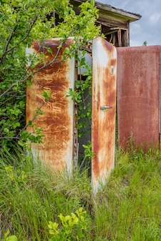 A rusty vintage fridge overgrown by shrubs outside on the prairies